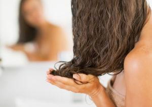 Closeup on young woman applying hair mask